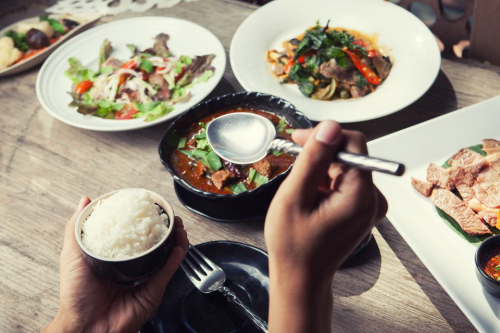 hand-holding-spoon-and-dinner-with-thailand-food-hot-and-spicy-with-herb-on-wooden-table-639948508-5a91c620642dca0036f0c212